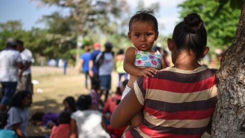 Una mujer con una menor en la caravana de migrantes que está en M...