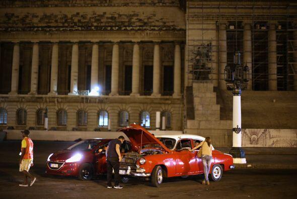 Un coche nuevo de la marca Peugeot aparca a lado de un Chevrolet Bel-Air...