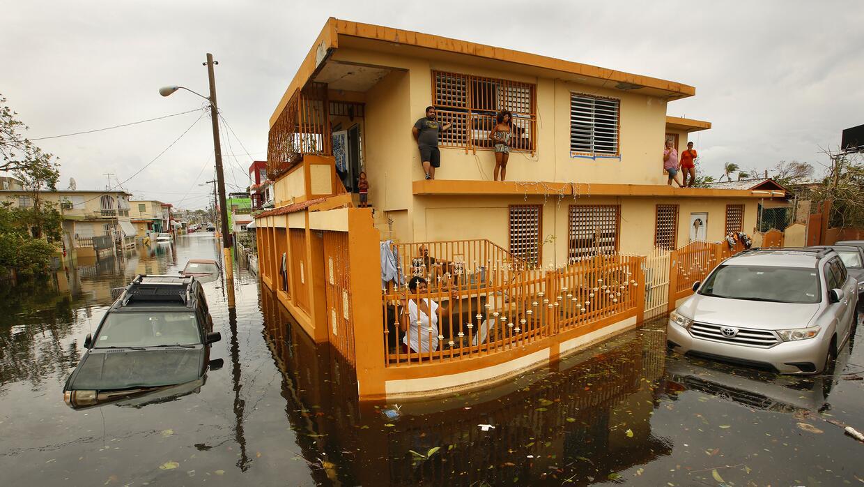 Una familia se pone a salvo de las extensas inundaciones que el huracán...