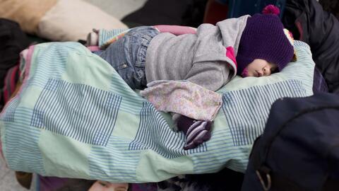 Una niña duerme encima de maletas en la ciudad fronteriza de Rumi...