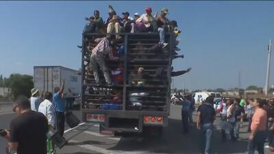 Tras una noche de frío intenso, miembros de la caravana migrante siguen su rumbo hacia EEUU