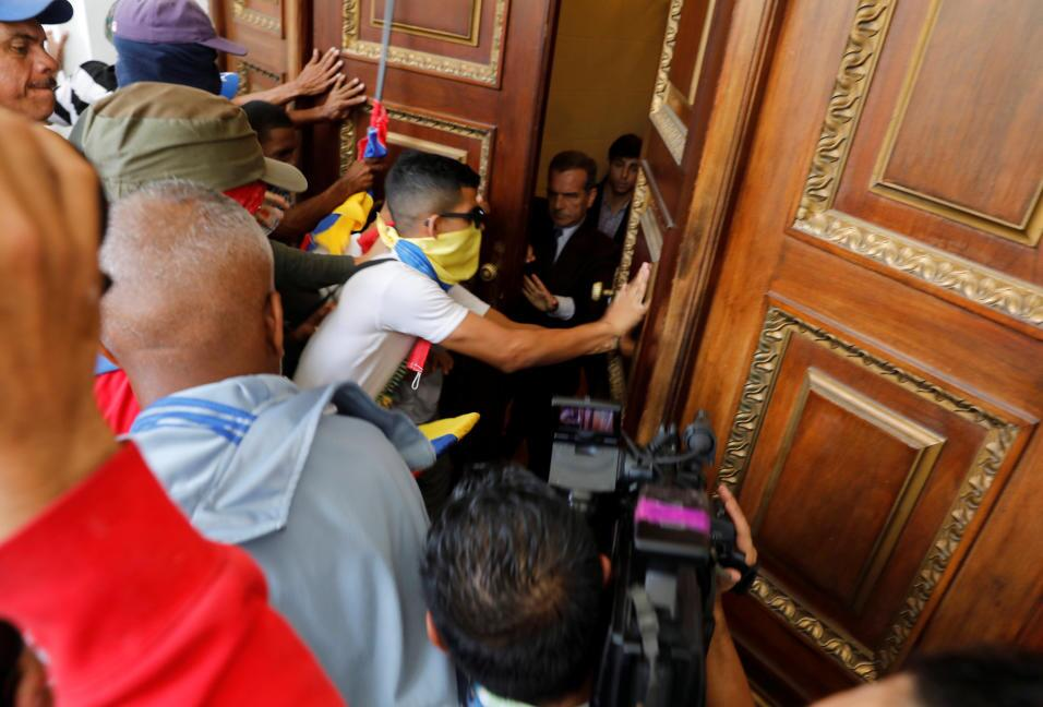 Pro-government activists try to break through the doors of parliament. T...