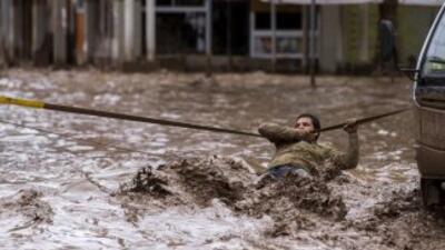 Este hombre se aferra a una cuerda para cruzar la calle tras el desborda...