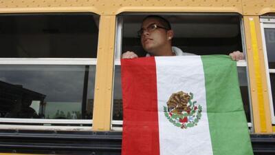 Un estudiante no identificado muestra la bandera mexicana mientras anda...