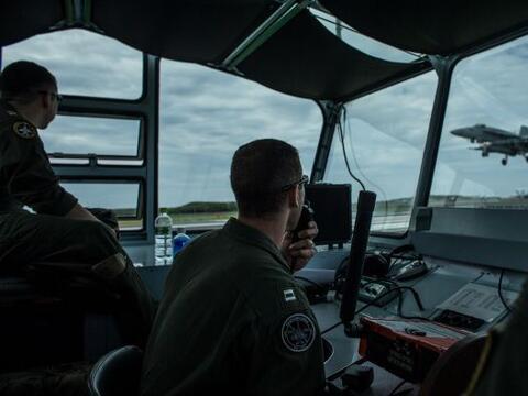Oficiales de aterrizaje ven como un piloto completa su descenso-despegue...