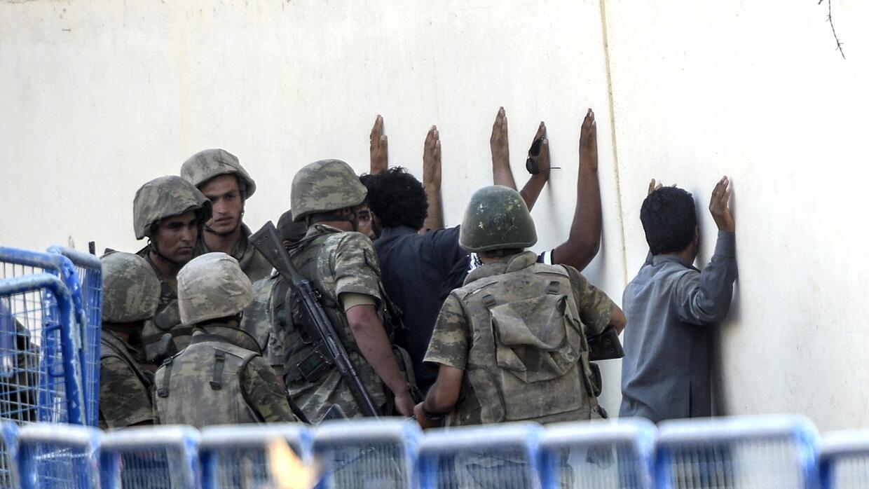 Soldados turcos arrestan a un grupo de hombres en un tramo de la fronter...