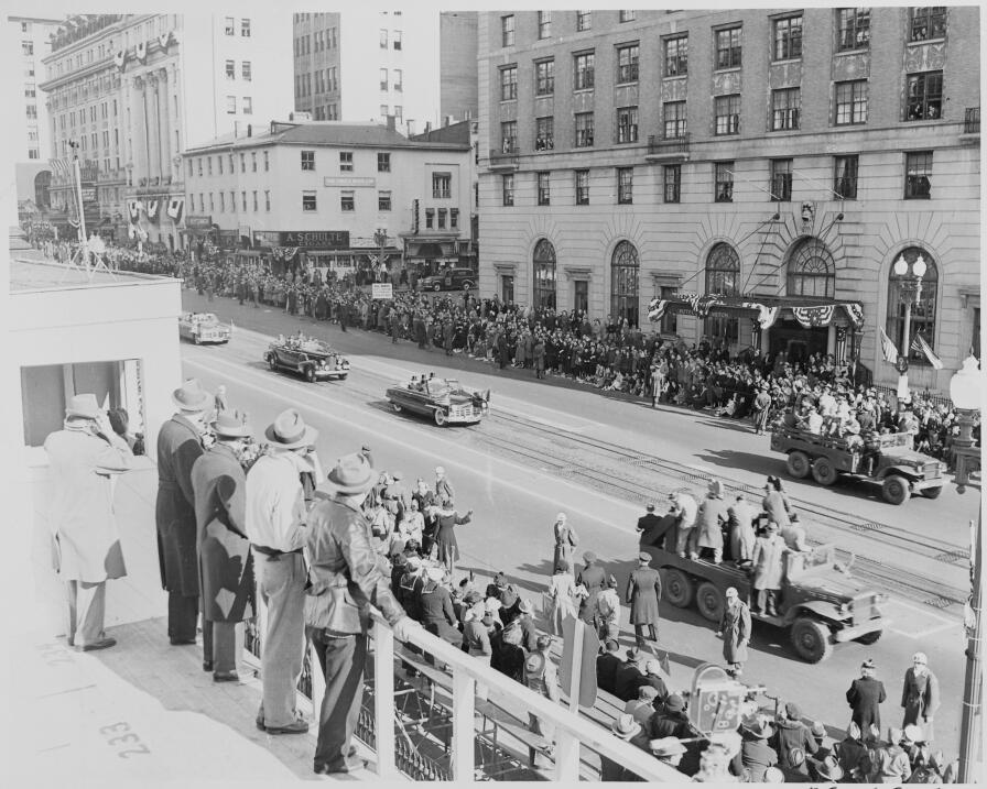 Distance view of President Truman riding in his limousine to the reviewi...