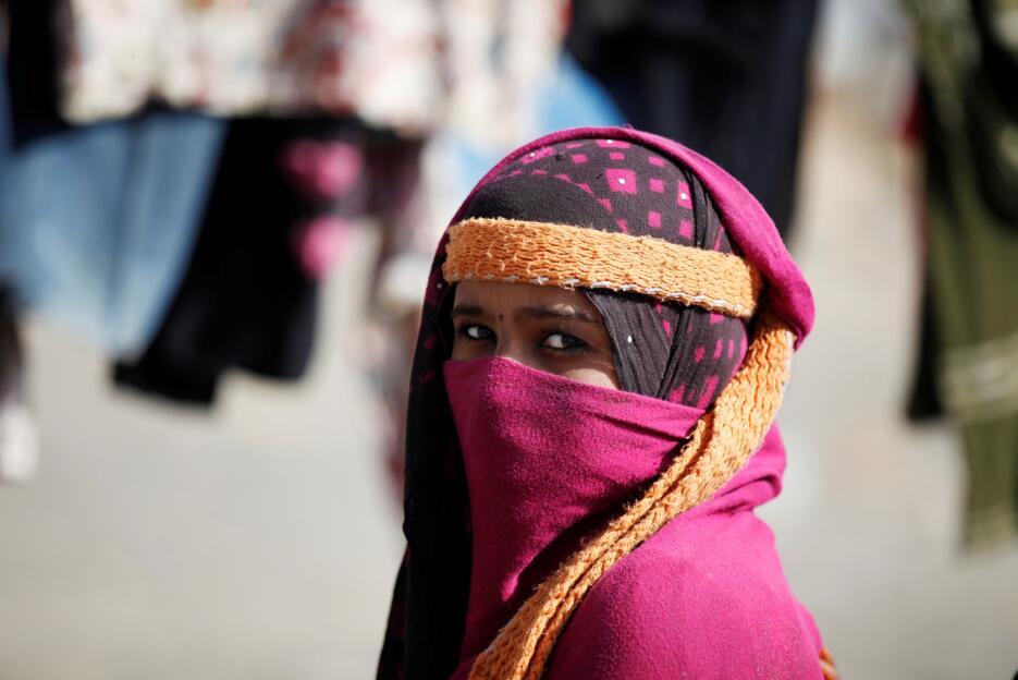 Yemen: Una mujer observa junto a su tienda en el campo de desplazados de...