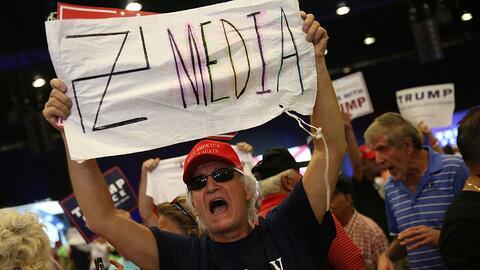 Un simpatizante de Trump en su mitin de West Palm Beach muestra un carte...