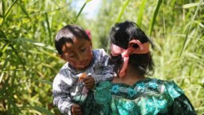 Una madre inmigrante lleva a su hijo en brazos por un sendero en la frio...