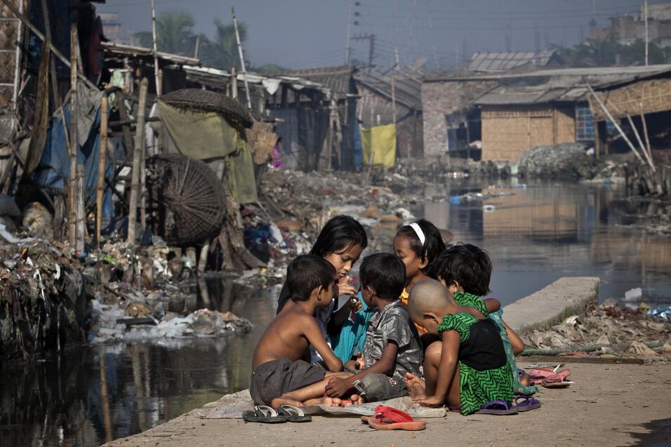 Niños juegan fuera de su casa, al lado de un canal contaminado por la in...