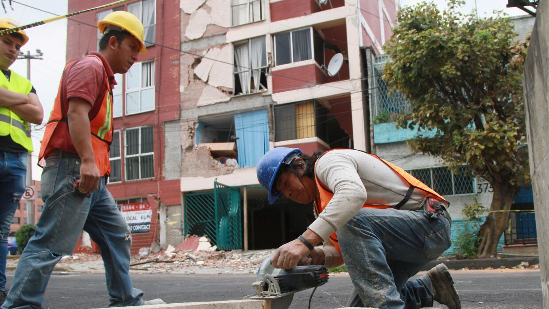 Dos hombres  cortan vigas para colocarlas en un inmueble de la Ciudad de...