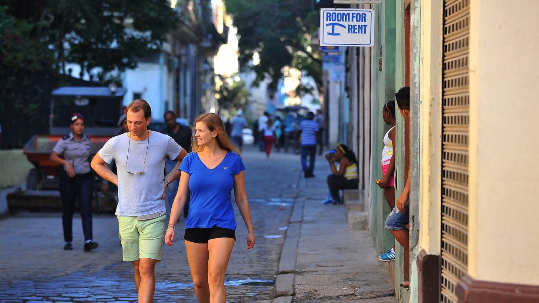 En la fotografía, los turistas caminan al lado de una casa con una habit...