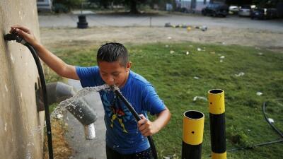 Niño bebe agua de un pozo con uranio en un parking de caravanas en Fresno.