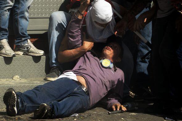 Los manifestantes auxilian a otro herido. Los estudiantes llevaron a cab...