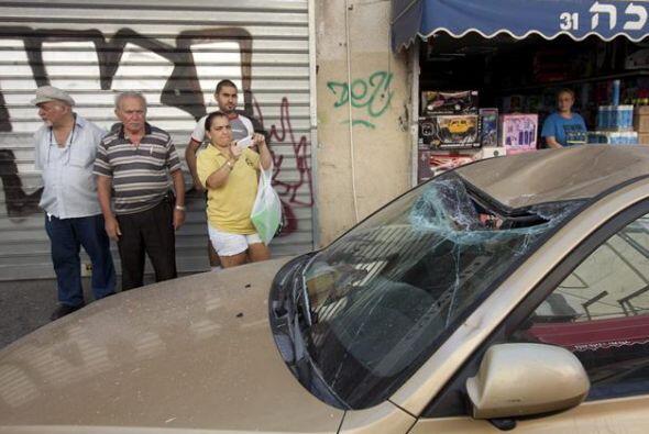 Varios israelíes inspeccionan los daños registrados en un...