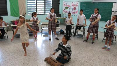 Brayan Lopez, de 9 años, toca un tambor de madera de Taino mientr...