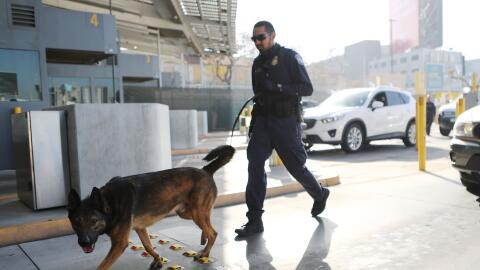 Un agente aduanal recorre con un perro antinarcóticos la garita d...