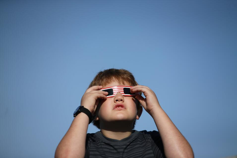 A boy uses solar viewing glasses as the sun emerges through fog cover be...