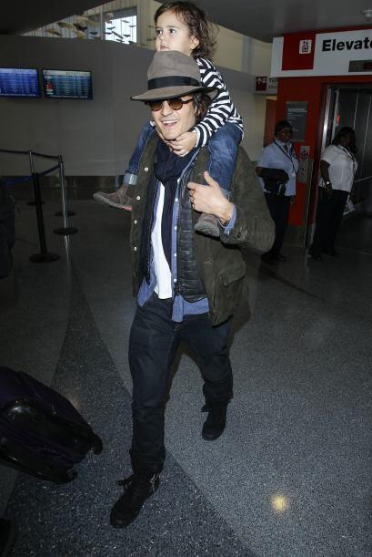 Orlando Bloom lleva a su hijo Flynn en sus hombros a su llegada al aerop...