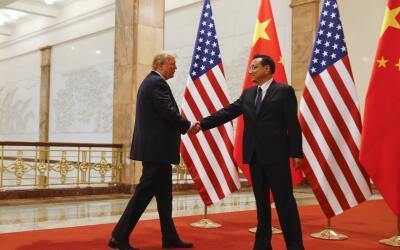 El presidente Donald Trump da la mano al premier chino Li Keqiang en nov...