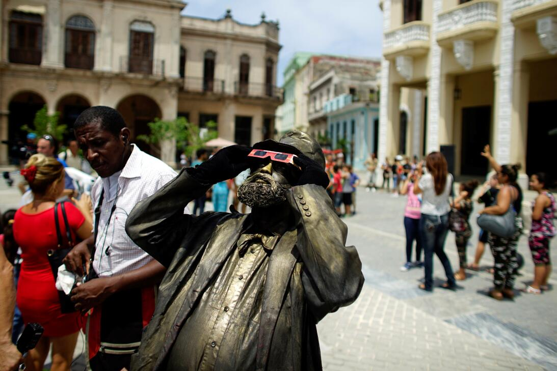 A street performer looks towards the sky as enthusiasts gather in Old Ha...