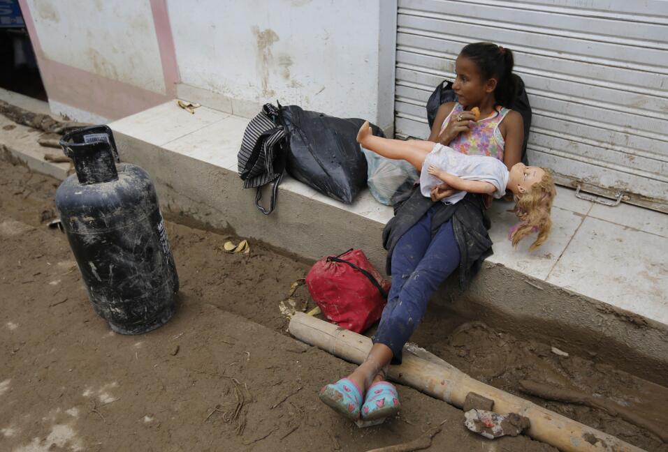 Una niña con su muñeca que logró rescatar de su casa afectada por la inu...