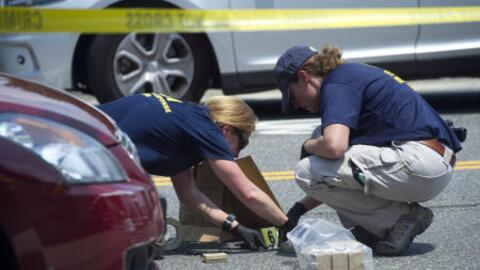 FBI agents collect evidence at the scene of a shooting in Alexandria, Vi...