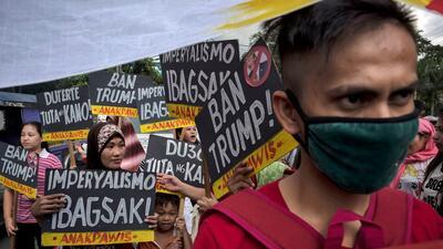 """FOTOS: Con pancartas de """"despidan a Trump"""" y represión policial, manifestantes reciben en Filipinas al presidente"""