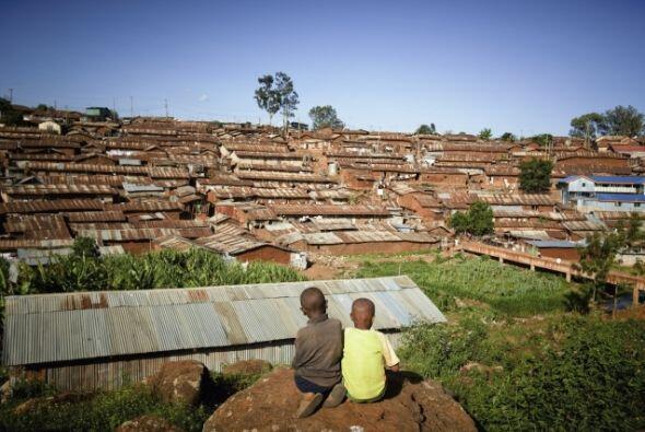 Niños se sientan en una roca con vista al barrio marginal de Kibera, en...