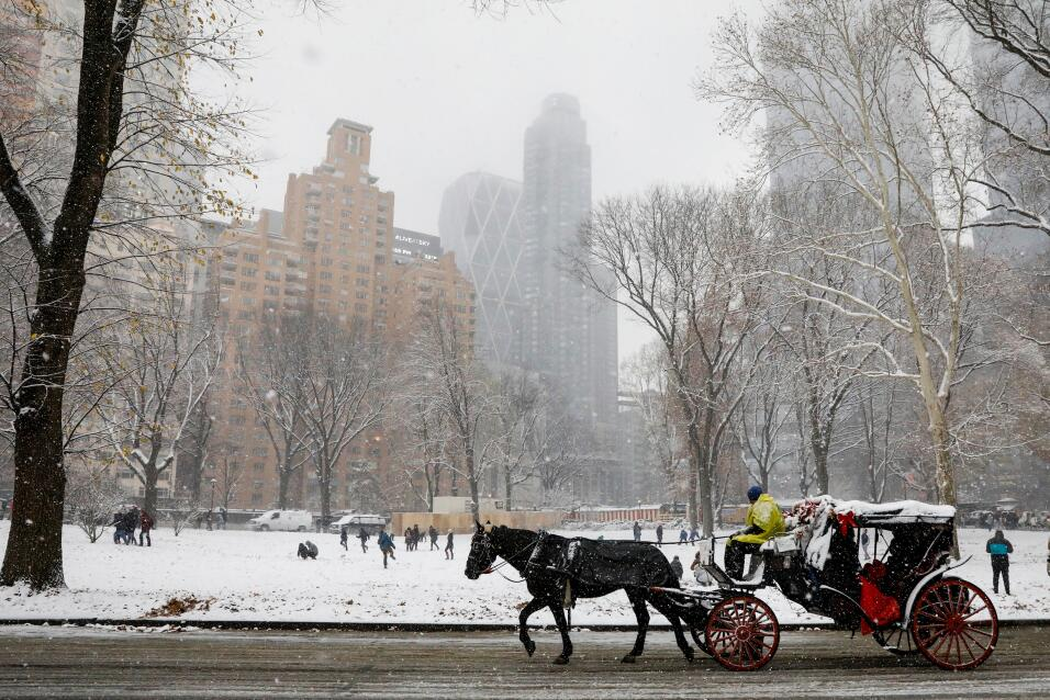 A horse pulls a carriage through Central Park as the snow falls during a...
