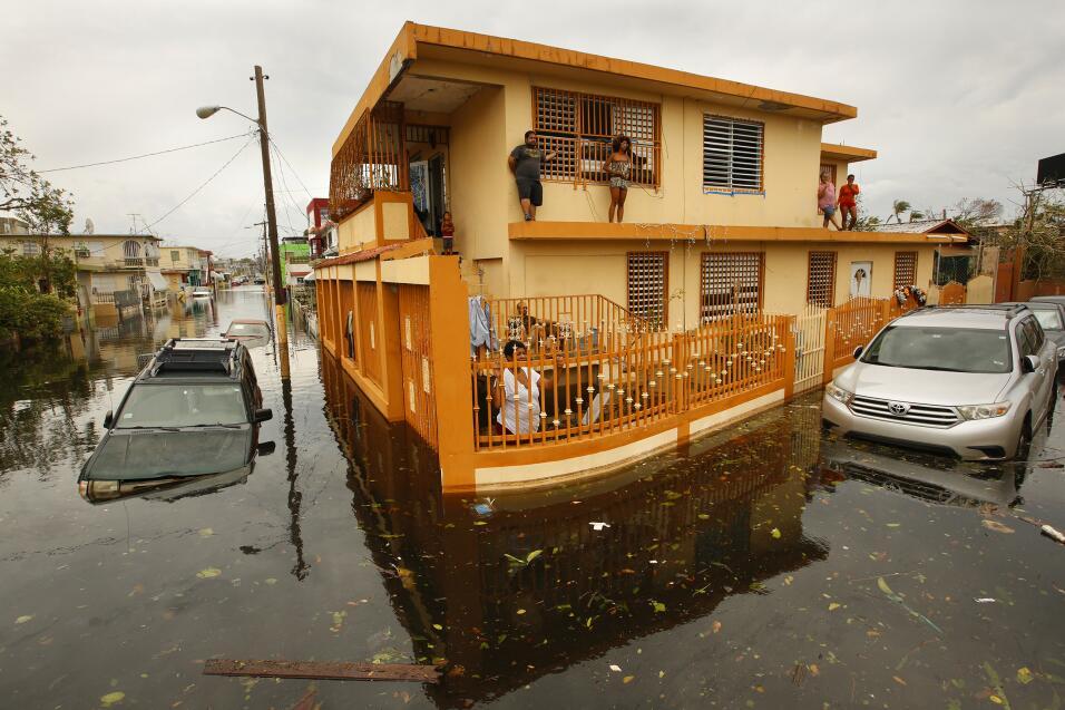 Una familia se pone a salvo de las extensas inundaciones que el hurac&aa...