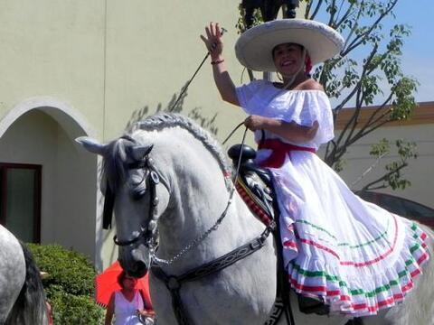 Una mujer con atuendos tradicionales de México participa en un de...