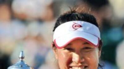La tailandesa, Tamarine Tanasugarn, posa junto al trofeo ganado en Osaka.
