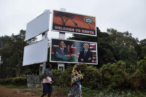 Peatones caminan bajo un enorme cartel con los presidentes Obama y Kenya...