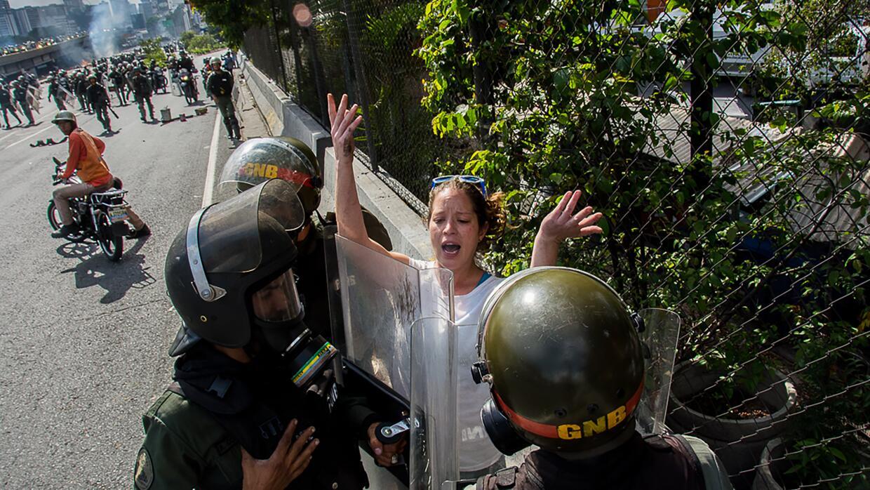 Tres soldados de la Guardia Nacional detienen a una manifestante en Cara...