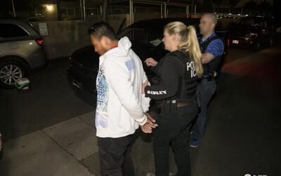 Agentes de ICE conducen a uno de los 115 arrestados en un operativo en l...