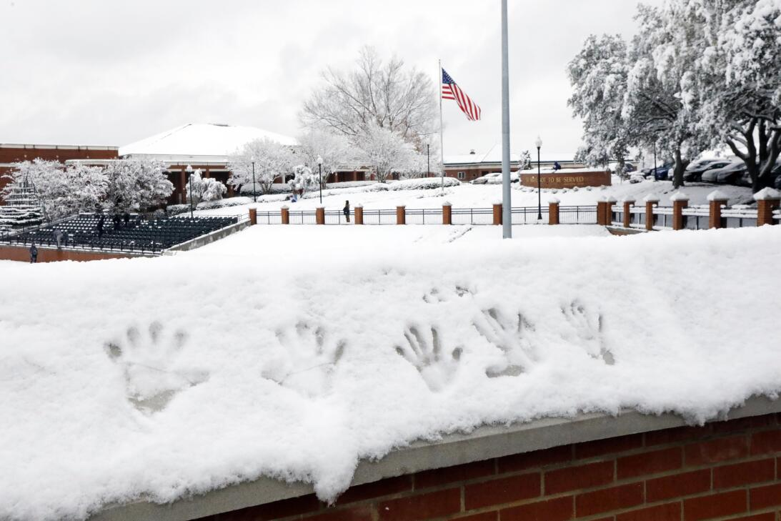 Belhaven University students leave their handprints in the snow on the l...