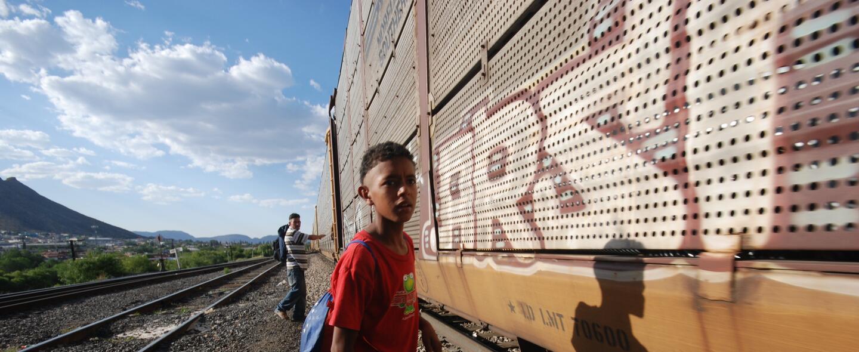 Un niño espera el momento indicado para subir al tren de carga que lo ll...