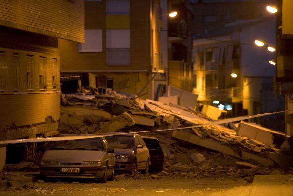 El panorama de la ciudad es triste, lleno de escombros, automóviles y ed...