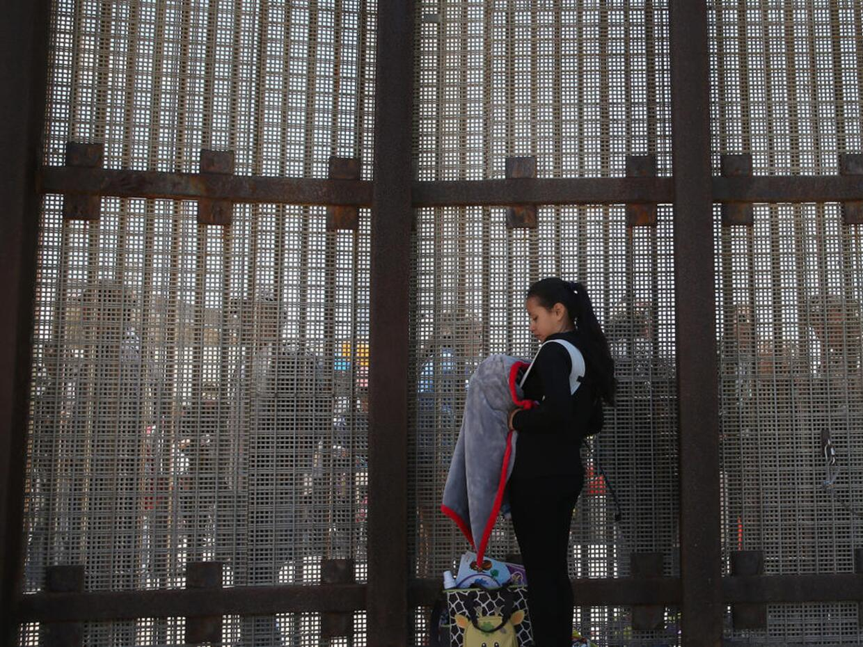 Karen Herrera, 23, and her infant son Ivan, on the border in San Diego,...