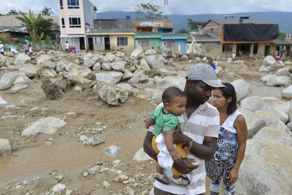 Una familia en Mocoa, Colombia revisa los daños causados por las inundac...