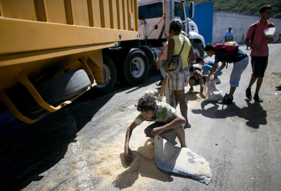 Un joven utiliza una funda de almohada para recoger arroz del pavimento...