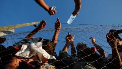 Un hombre macedonio vende agua a refugiados y migrantes en un campo de a...