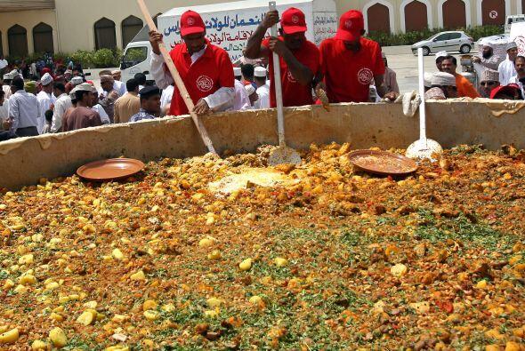 Hombres de Omán revuelven los ingredientes para preparar uno de s...