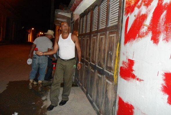 Los paramilitares borran los carteles pintados por los opositores cubanos.