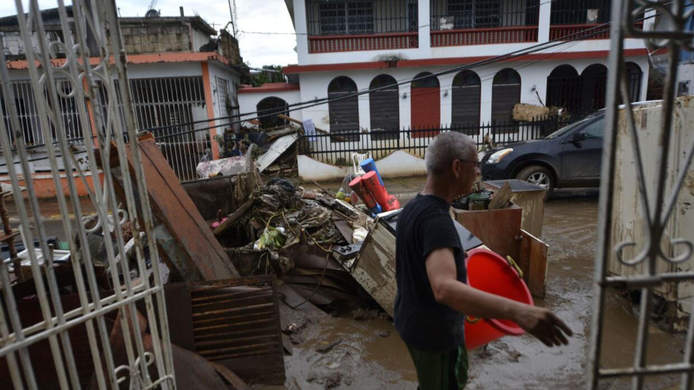 Víctor Otero sale de su casa inundada en el municipio de Toa Baja, tras...