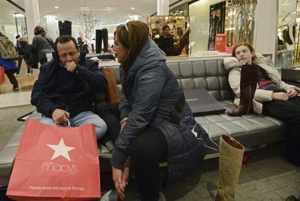 Después de una noche de compras, unos cansados clientes descansan en los...