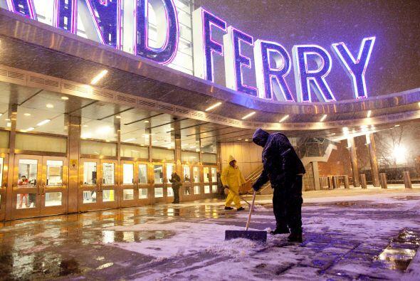 Trabajadores despejan la nieve en la entrada de la estación del Ferry en...