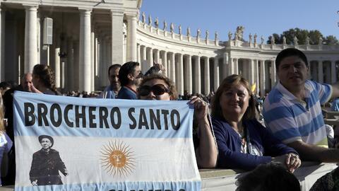 """Fieles argentinos sostienen una bandera del """"sacerdote gaucho""""..."""